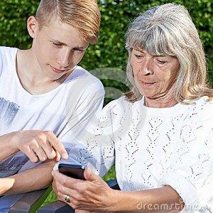 teen-senior-smartphone-young-man-teaching-elderly-woman-to-use-31053128