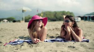 stock-footage-two-girlfriends-lying-on-beach-and-chatting